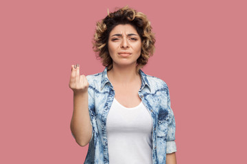 Portrait of serious young woman with curly hairstyle in casual blue shirt standing with money or italian gesture and looking at camera. indoor studio shot, isolated on pink background.