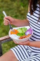 femme mangeant un poke bowl hawaïen dans le jardin