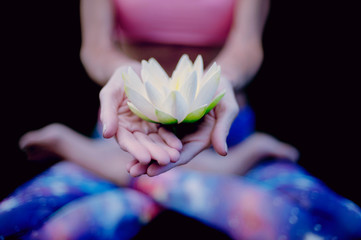 Yoga woman holding lotus blossom.