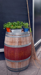barrel with herbs on top with a broom