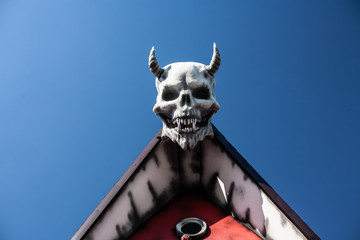 Devil head with horns on the roof of the house. Background.