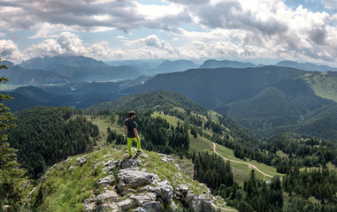 Outdoor panorama of hiker standing in green countryside with foggy valley in summer