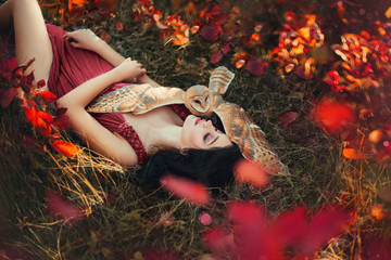 bright photo in burgundy shades, girl in dark dress color of Marsala, lady with dark hair lies on grass, fallen red and yellow leaves, barn owl spread its wings on sleeping fairy and protects sleep Fototapete