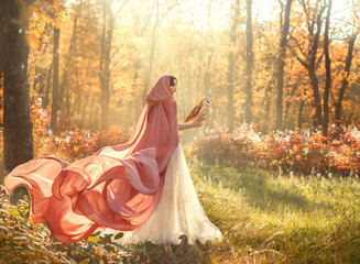 bright summer photo of mysterious beauty in morning forest, lady in shiny white dress and peach pink cloak with long train and hood, back to camera and turned face, girl with dark hair and barn owl