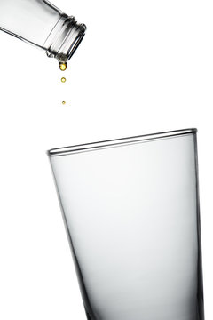 Empty bottle with last drops of beverage dripping into  empty glass. Stop action closeup isolated on white background