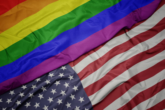 waving colorful flag of united states of america and gay rainbow flag.