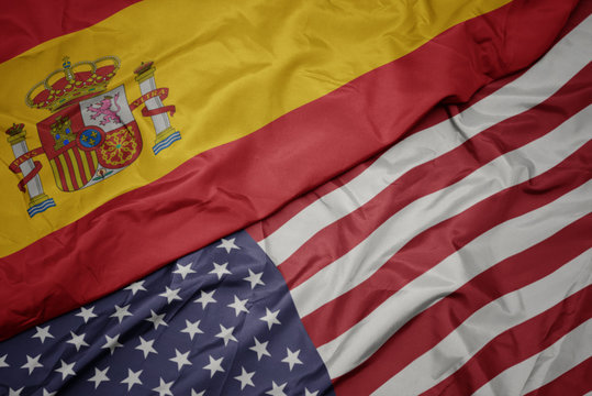 waving colorful flag of united states of america and national flag of spain. macro