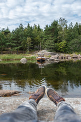 Fototapeta Antique, wooden boat. Northern nature, sea bay and huge stones. The coastline of a rocky island. Scandinavian nature
