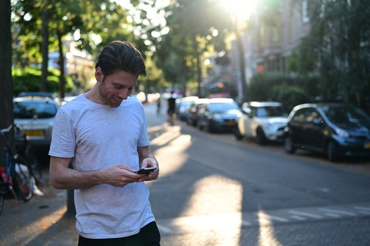 Spontaneous young man smiling and texting his friend on his mobile phone while standing in a ambient street