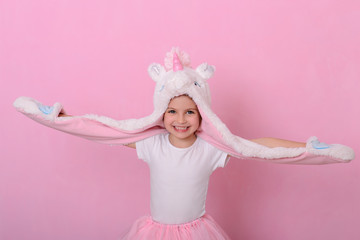 Caucasian beautiful little girl in a hat with  unikorn  on a pink background.