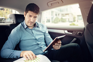 Young businessman traveling into a limo while checking papers and using a tablet
