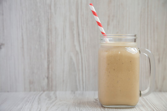 Tasty peanut butter banana smoothie in a glass jar mug, side view. Close-up. Space for text.
