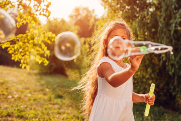 Little cute girl blowing bubbles in summer park. Kid having fun outdoors