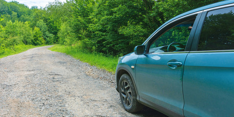 suv on the old forest road. cyan blue vehicle parked on the cracked asphalt way uphill among trees. view from the drivers door and side mirror. lost direction or navigation concept. abandoned car