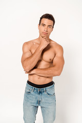 pensive mixed race man touching chin while standing in blue jeans on white