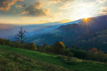 amazing foggy sunrise in autumn. beautiful mountain landscape at dawn. trees on the hill in fall foliage. clouds on the sky