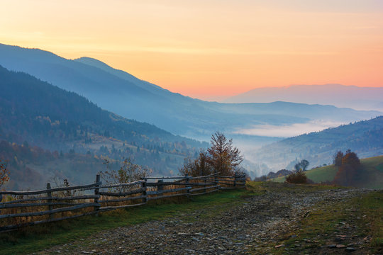 amazing beautiful rural area at dawn. morning in the carpathian mountains. fog in the distant valley. fence along the gravel road