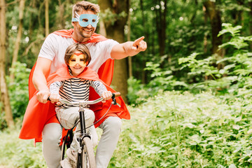 father and kid riding bicycle around forest in superhero costumes
