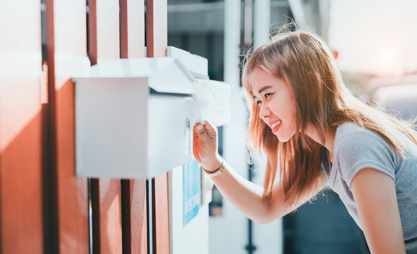 Beautiful asian woman open letter box checking at front home, Delivery message bills order receive to sender concept.