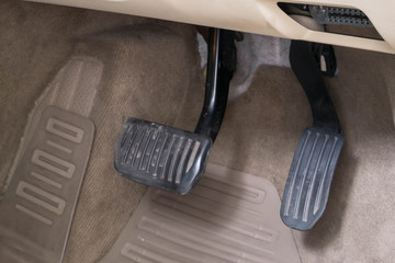 Luxury white car brake and acceleration pedals.