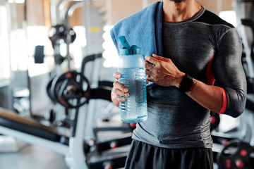 Cropped image of sportsman standing with towel on his shoulder and drinking bottle of fresh water between sets