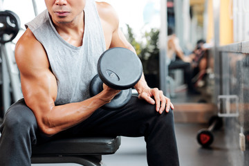 Cropped image of sporty serious man sitting on bench in gym and lifting heavy dumbbell