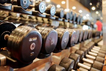 Deurstickers Fitness Rows of dumbbells of various weights and sizes in gym, selective focus