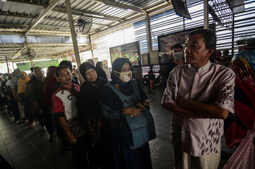 Passengers queue to refund their tickets during a major power blackout at a commuter train station in Jakarta