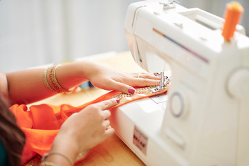 Close-up image of Indian seamstress attaching lace with embroidery to the sari dress