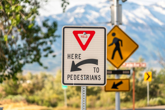 Yield Here To Pedestrians sign against trees and mountain viewed on a sunny day