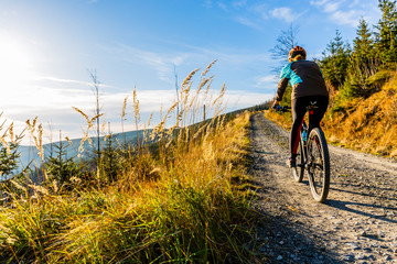 Mountain biking woman riding on bike in summer mountains forest landscape. Woman cycling MTB flow trail track. Outdoor sport activity. Wall mural
