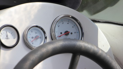 Modern motor boat telemetry, white analog appliance on dashboard in cockpit on steering wheel background - tachometer, trim control and fuel meter