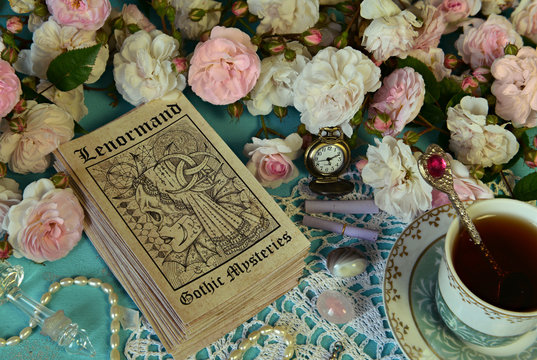 Still life with Lenormand tarot cards, roses and cup.