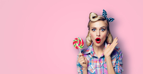 Excited surprised woman with lollipop. Girl pin up with open mouth. Blond model at retro fashion and vintage concept. Pink color studio background.