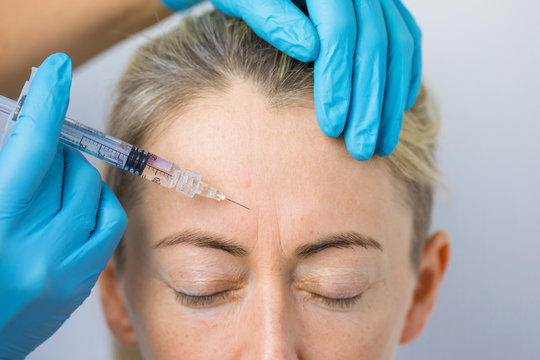 Doctor makes the rejuvenating facial injections for smoothing woman's forehead skin