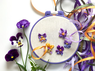 The process of embroidering with satin ribbons a floral ornament of yellow and violet pansy flowers or garden viola tricolor (the embroidery made the author of photo)