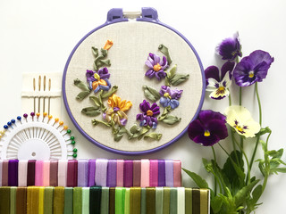 Embroidery with satin ribbons of yellow and violet pansies. Sets of pins, needles and multicolour ribbons on white background. Flat lay, close up, still life (the embroidery made the author of photo)