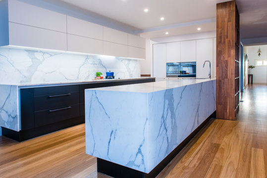 Modern open plan contemporary kitchen with marble island bench, countertops and back splash in Australian home