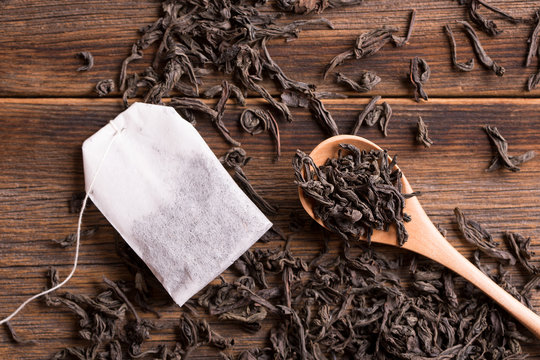 Tea in a wooden spoon and a tea bag. Loose tea in a spoon and tea bag on a wooden background.