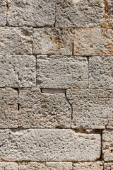 Old beige stone wall background texture, close up