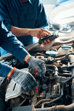 Hands of professional mechanics using professional tool for testing car motor in garage