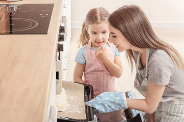 Little girl and her mother baking pastry in kitchen