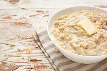 Bowl with tasty oatmeal on white wooden table