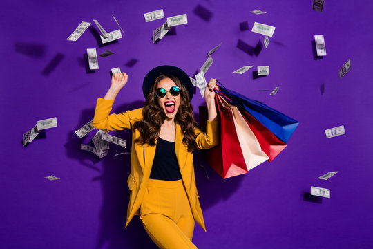 Portrait of her she nice lovely cheerful cheery glad wavy-haired lady shopaholic carrying bags flying 100 million budget salary success isolated over bright vivid shine violet lilac background