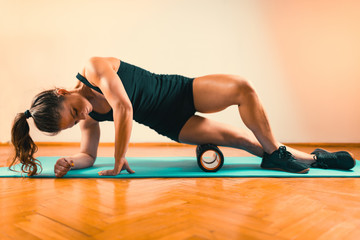 Woman Massaging Legs with Foam Roller