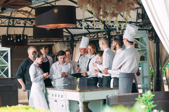 Restaurant manager and his staff in terrace. interacting to head chef in restaurant.
