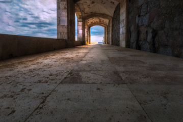 A charming scene taken inside a stone alley with some cloudy sky, symmetric perspective & dreamy...