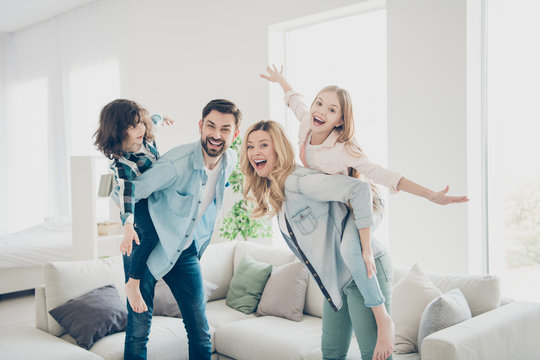 Profile photo of four family members having best free time pretend flight airplane indoors apartments
