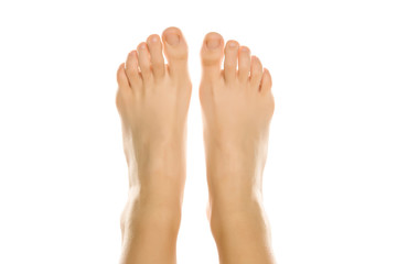 Young woman's beautiful bare feet and toes top view. Closeup isolated on white background.