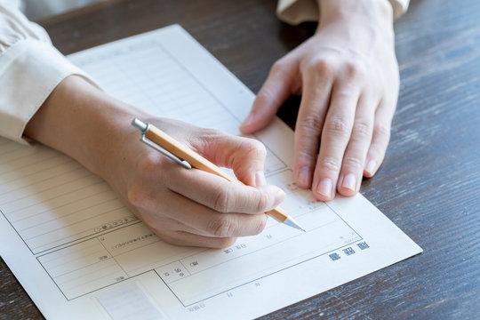 書類に記名する女性の手元